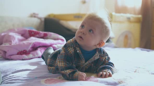 Little Baby in Warm Clothes Lies on Comfortable Bed in Room