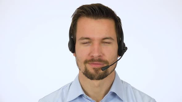 Thumbnail for A Young Handsome Call Center Agent Smiles at the Camera - Closeup - White Screen Studio