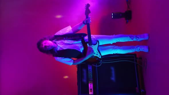 Vertical Video of an Energetic Male Rock Band Guitarist Playing in Neon Light and Smoke. Dancing