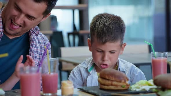 Thumbnail for Fast Food, Hungry Male Children with Their Father Eat Tasty Juicy Meat Burgers with French Fries and