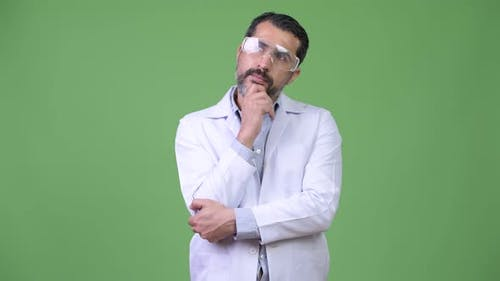 Happy Persian Bearded Man Doctor Wearing Protective Glasses While Thinking