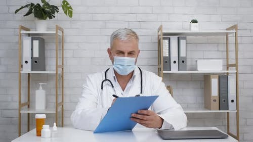 Doctor Wearing Face Mask Inviting On Medical Consultation In Office