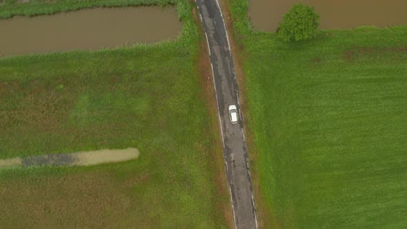 Thumbnail for Top Down Overhead Aerial View of Electric Vehicle Driving Trough Nature on Small Road Surrounded By