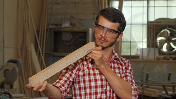 Thumbnail for Bearded Carpenter Examining Wood Piece After Grinding It
