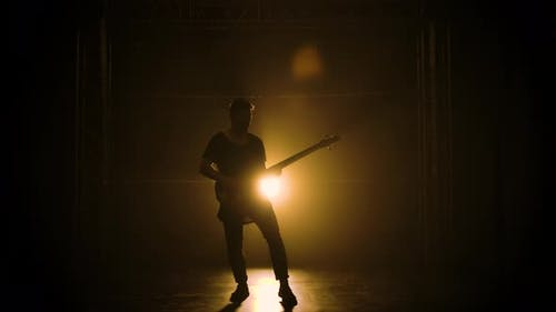 Silhouette of a Young Guy Playing on the Electric Guitar on Stage in a Dark Studio with Smoke