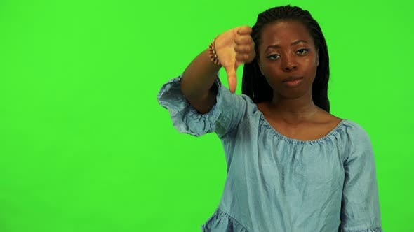 Thumbnail for A Young Black Woman Shows a Thumb Down To the Camera - Green Screen Studio