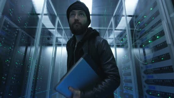 Hacker Sneaking Through Rows of Servers with Laptop