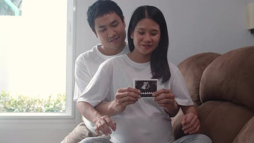 Young Asian Pregnant couple show and looking ultrasound photo baby in belly feeling happy smiling.