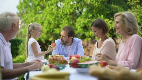 Daughter Treating Father With Watermelon, Family Having Fun While Eating Dinner