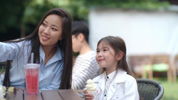 Thumbnail for Asian Woman Taking Selfie with Little Girl in Outdoor Cafe