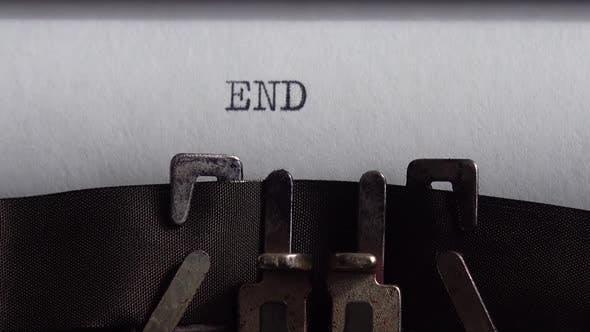 Typing word End on retro typewriter. Close up.