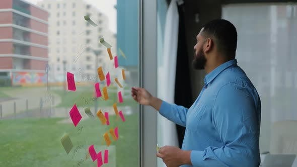 Thumbnail for Focused Bearded Man Changing Business Plan Written on Window