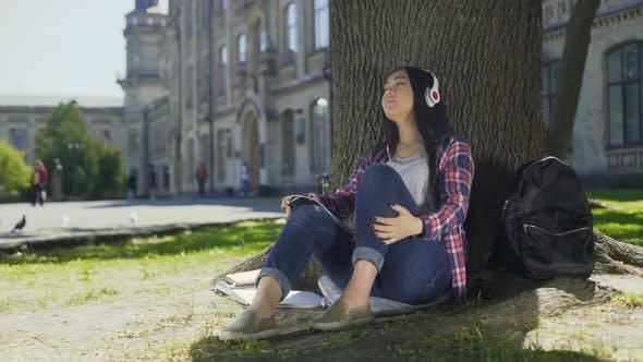 Thumbnail for Asian Female in Headphones Enjoying Music, Sitting Under Tree, Favorite Band