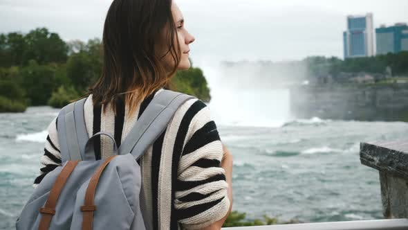 Thumbnail for Back View of Happy Local Caucasian Woman with Backpack Looking Right, Watching Waterfall at Niagara