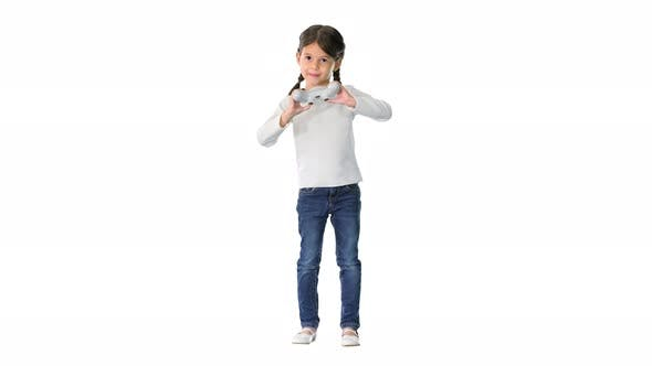 Excited Little Girl Play Videogame Holding Joystick in Her Hands on White Background