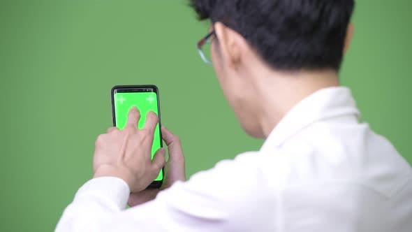 Young Asian Businessman Using Phone While Showing Copy Space