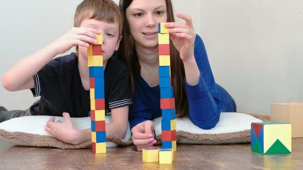 Thumbnail for Building a Towers From Blocks. Mom and Son Playing Together with Wooden Blocks