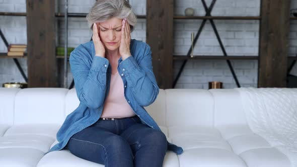 Thumbnail for Older Woman Sit on Sofa Coping with Headache