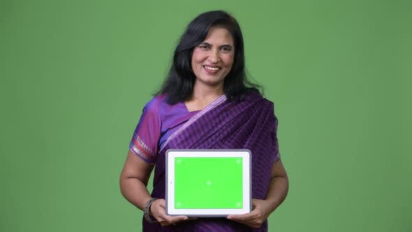 Cover Image for Mature Happy Beautiful Indian Woman Smiling While Showing Digital Tablet