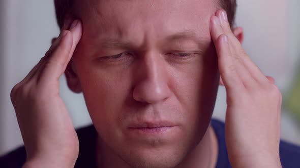 Portrait of a young man with severe headache massaging his temples, close-up
