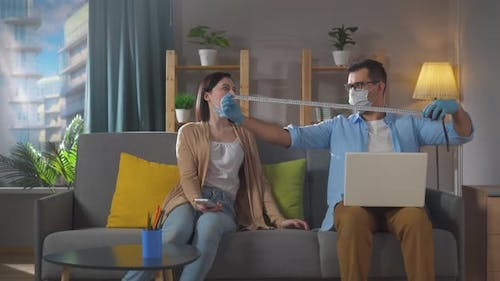 Man and a Woman Keep Their Distance at Home in Quarantine Humor