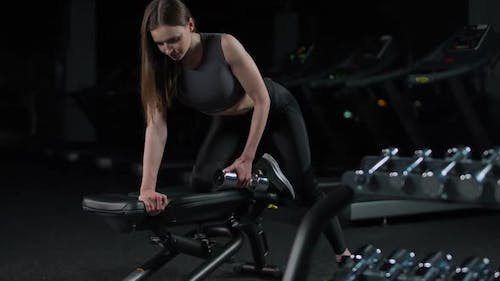Young Woman in the Gym Girl Lifts a Dumbbell in a Tilt Muscle Training with Weights