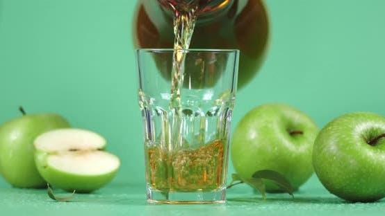 Gießen Sie frischen Apfelsaft in ein Glas.