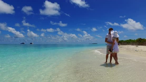 Thumbnail for Young couple in love dating on vacation live the dream on beach on paradise white sand background 4K