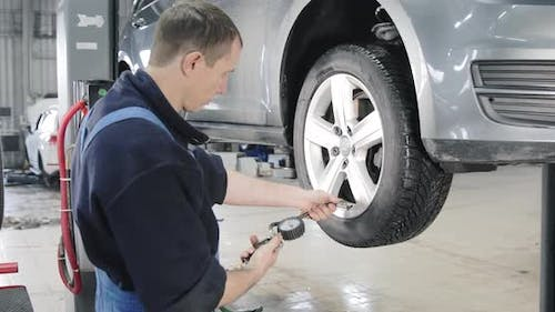 Close Shot Of Mechanic Inflating A Tire With Compressor