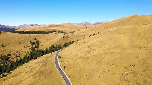 Thumbnail for Aerial view of car driving down country road through rural rolling hills and mountain