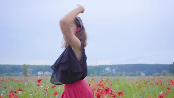 Cover Image for Pretty Young Woman Wearing Headphones Listening To Music and Dancing in a Poppy Field Smiling