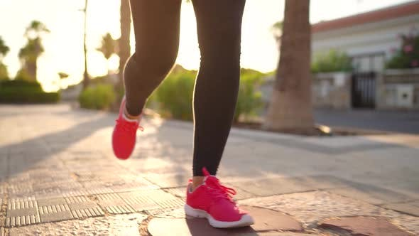 Close Up of Legs of a Woman Running Along the Palm Avenue at Sunset