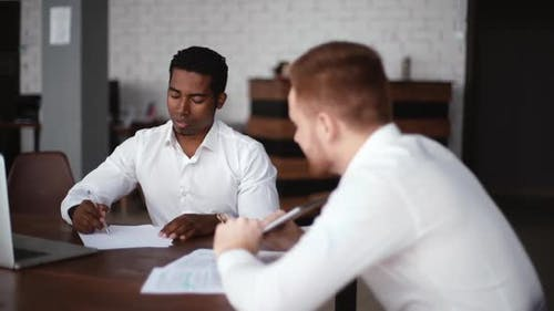 African American Black Businessman and Caucasian European Business Partner Preparing the Contract.