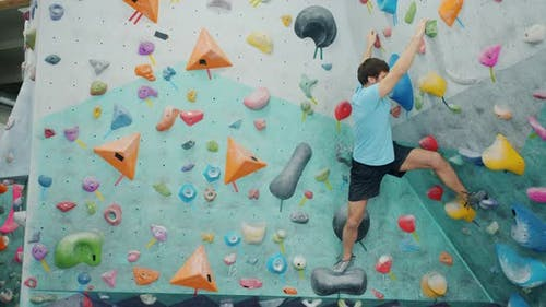 Strong Guy in Sports Outfit Climbing Up Colorful Artificial Wall in Gym Gripping Rocks