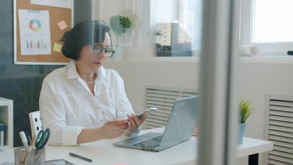 Cheerful Woman Using Laptop Typing Then Talking on Mobile Phone and Smiling Working in Office Alone
