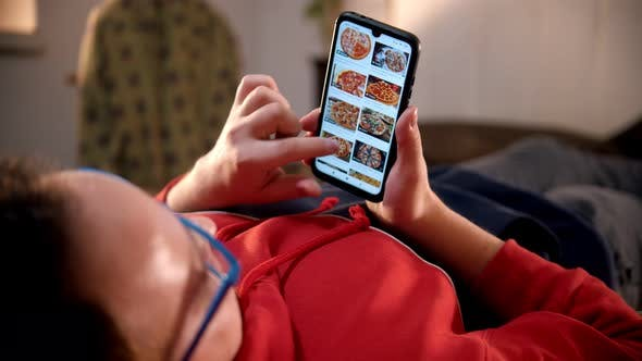Thumbnail for Young Man Lying on the Bed and Scrolling Pictures of Pizza on His Phone
