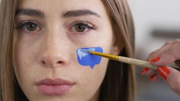 Nahaufnahme Porträt von Junge Pleasant Frau Blick auf Kamera während Künstler Malerei Nachricht Box