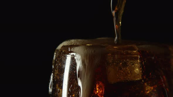 Thumbnail for A Cola Drink Are Pouring In Glass With Ice On A Black Background