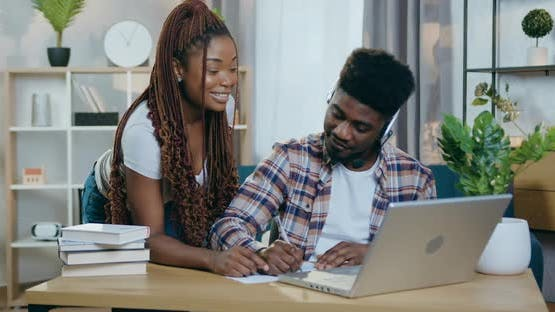 African Couple with Positive Emotions Looking on laptop