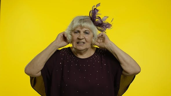 Annoyed Irritated Senior Old Woman Covering Ears and Gesturing No, Avoiding Advice, Ignoring Noise
