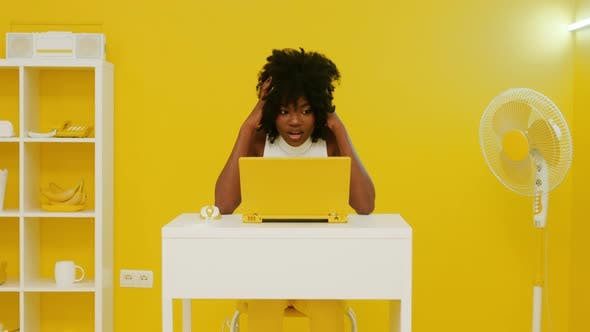 Astonished African Woman Is Working at Laptop