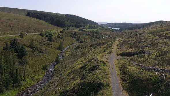 A Flight Over a Valley with a Mountain Road Running Past It