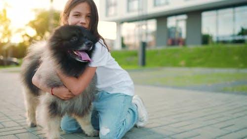 Brunette Girl Hugs a Fluffy Dog at Sunset Outdoors