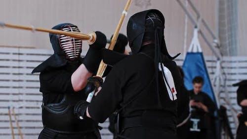 Kendo Turnier in der Schule Gym Zwei Männer in schwarzen Kostümen haben ein Duell auf Bambusstöcken