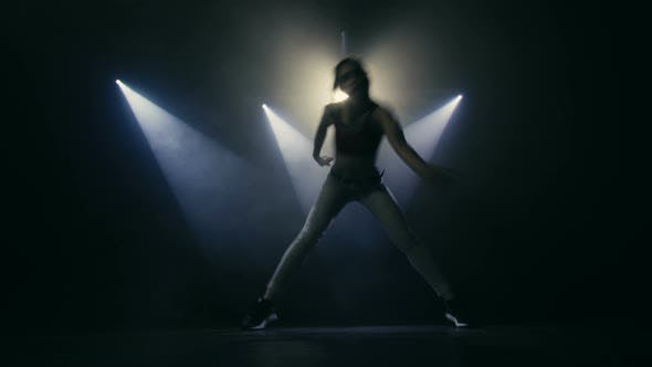 Thumbnail for Beautiful Young Woman Dancing Hip-Hop On Stage In The Rays Of Light And In The Smoke