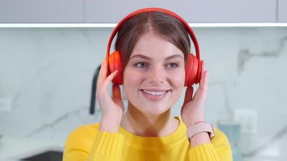 Thumbnail for Junge kaukasische schöne lockige Frau in Kopfhörern Hören der Musik und Scrollen oder Tippen