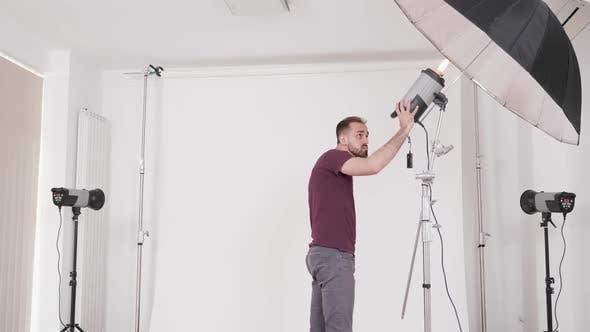 Thumbnail for Mittlere Aufnahme eines Fotografen in einem Studio Einrichtung der Ausrüstung