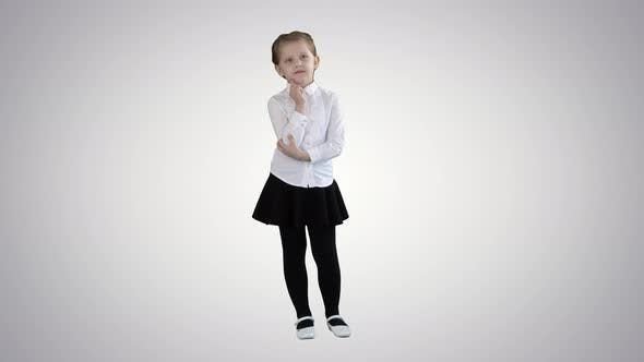 Cover Image for A Curious Little Girl Stands and Thinks on Gradient Background.