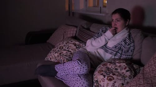 Young Woman Watching a Scary Movie in the Dark
