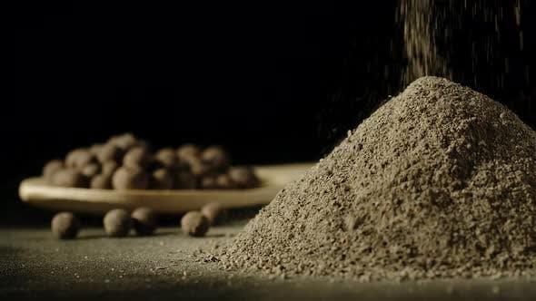 Black pepper powder pouring in a heap next to black peppercorns